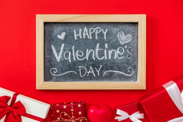 Testo scritto a mano di san valentino felice sulla lavagna con il contenitore di regalo