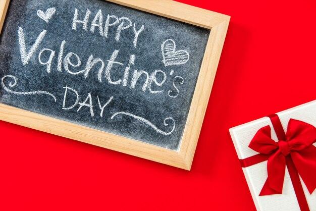 Testo scritto a mano felice di san valentino sulla lavagna con il contenitore di regalo