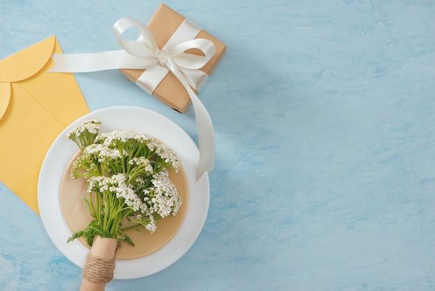 Tet concetto di vacanza. busta d'oro (denaro fortunato) sul tavolo con tavola con piatto e fiori.