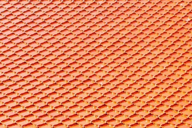 Tetto di mattonelle arancioni al tempio buddista. sfondo del modello quadrato.