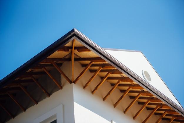 Tetto di tegole di un cottage bianco a due piani