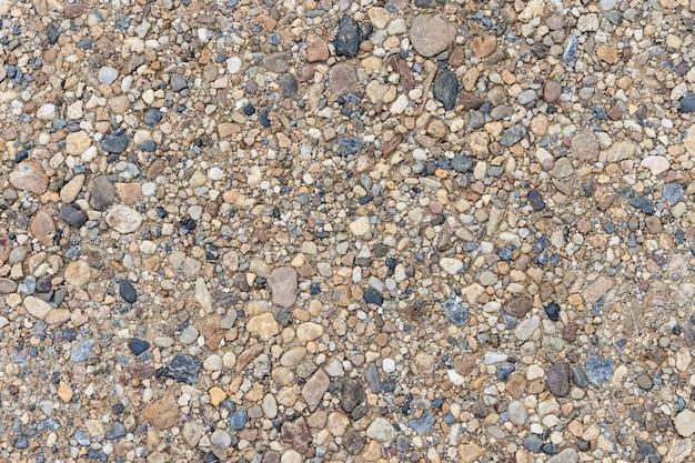 Texture colorate di sabbia o ciottoli. struttura senza cuciture su terra.