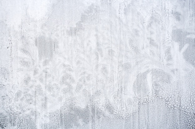 Texture di neve ghiacciata sul vetro della finestra a forma di piante fantastiche.