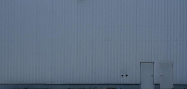 Texture di un alto muro di metallo di un edificio industriale senza finestre