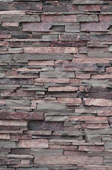 Texture di un muro di pietra da pietre lunghe e ruvide di diverse dimensioni e toni