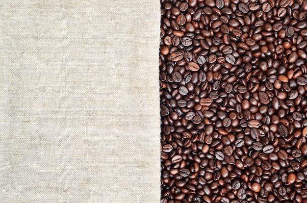 Texture di una tela grigia fatta di vecchia e ruvida tela con chicchi di caffè su di esso