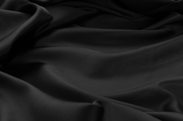 Texture la superficie del tessuto in tessuto increspato in raso nero ci ha utilizzato per la progettazione di prodotti di lusso sullo sfondo