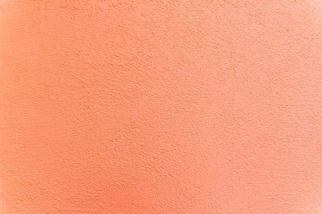 Texture, muro, cemento, color corallo vivente. frammento di muro con graffi e crepe. stucco decorativo antico, intonaco.