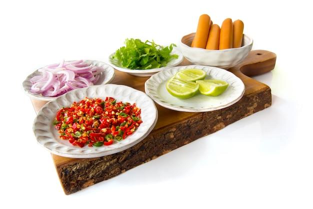 Thai cuisine ingrediente di salsiccia piccante insalata di scalogno, salari, limone, peperoncino rosso, uovo salato su tagliere di legno