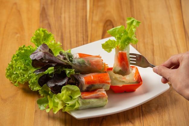 Thai salad rolls con salsa piccante all'aglio disposta su un pavimento di legno.
