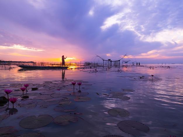 Thailandia pescatore lanciare la rete da pesca catturare il pesce provocando spruzzi d'acqua