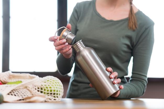 Thermos della bottiglia di apertura della donna del primo piano