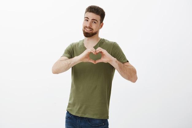 Ti amo piccola. affascinante uomo barbuto attraente che mostra il segno del cuore vicino al petto.