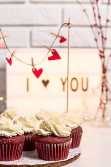 Ti amo scritto su una lampada decorativa accanto ai cupcakes rossi