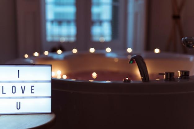 Ti amo titolo sulla lampada vicino alla vasca idromassaggio con candele accese