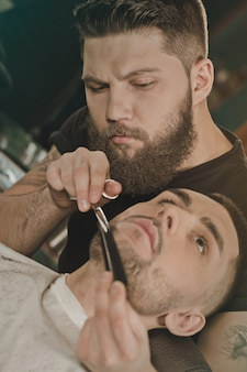 Ti modellerà nel modo giusto. colpo verticale di un giovane in una bottega del barbiere che si fa tagliare e modellare la barba