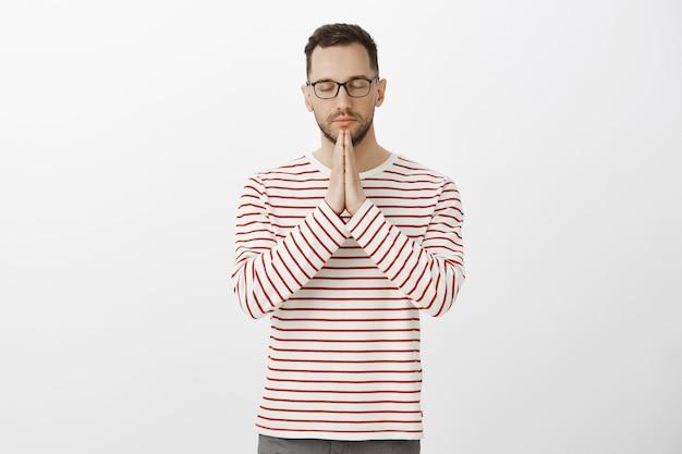 Tieni i sentimenti sotto controllo. ritratto di padre adulto bello calmo concentrato in occhiali eleganti e camicia a righe, tenendosi per mano in preghiera, chiudendo gli occhi e pregando o sperando, desiderando che dio lo ascolti