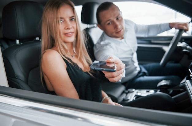 Tieni il telefono per un momento. gestore positivo che mostra le caratteristiche della nuova vettura al cliente femminile