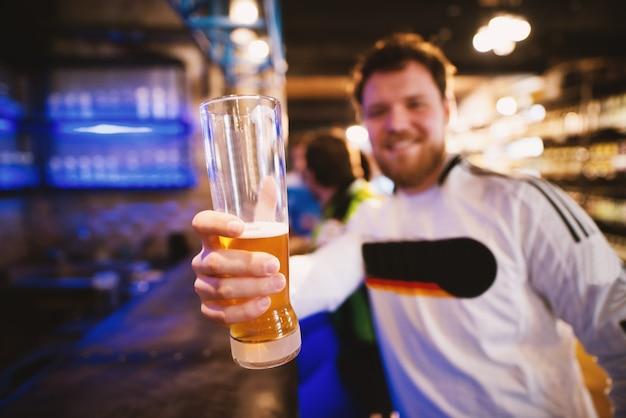 Tifoso che tiene una pinta di birra mentre seduto al bar in un pub.