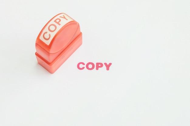 Timbro di gomma della pompa del primo piano con la parola rossa della copia dell'inchiostro su bianco