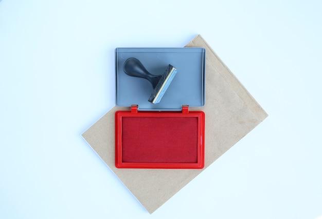 Timbro di gomma e cartucce di inchiostro rosso sul libro marrone su sfondo bianco.