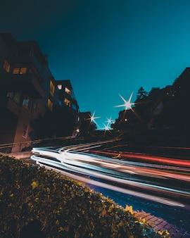 Timelaps di luci auto sulla strada con un cielo blu di notte