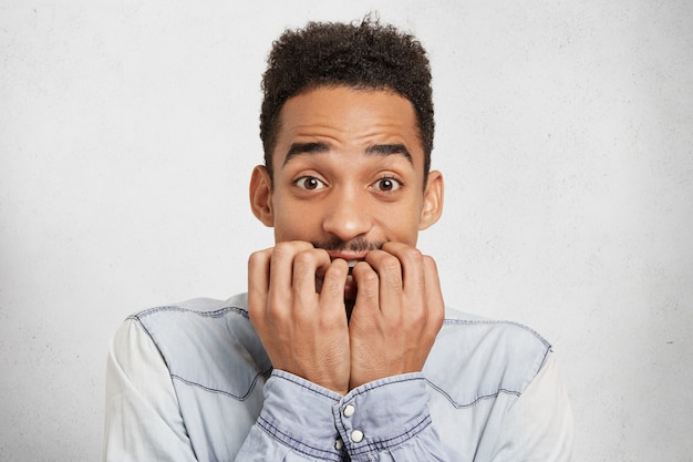 Timoroso uomo preoccupato morde le unghie in ansia, si sente nervoso