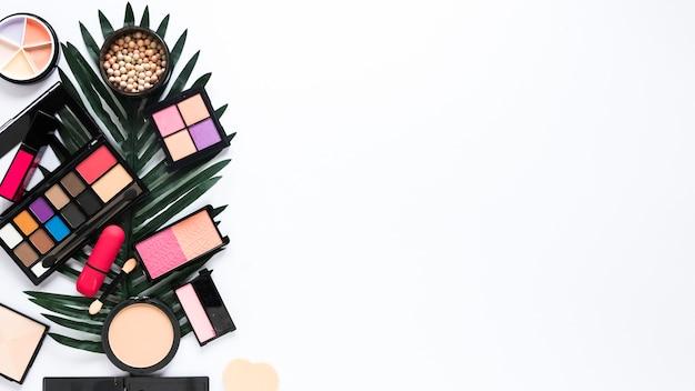 Tipi di cosmetici diversi con foglia verde sul tavolo bianco