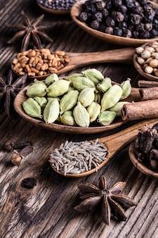 Tipi differenti di intere spezie indiane nel fondo di legno.