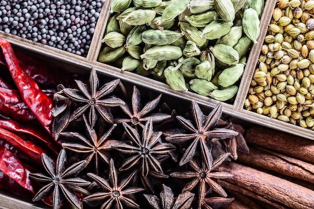 Tipi differenti di intere spezie indiane nella vista superiore del primo piano di legno della scatola.
