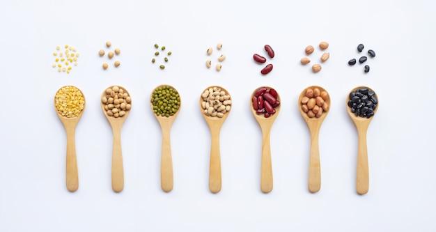 Tipi differenti di legumi sul cucchiaio di legno, fondo bianco.