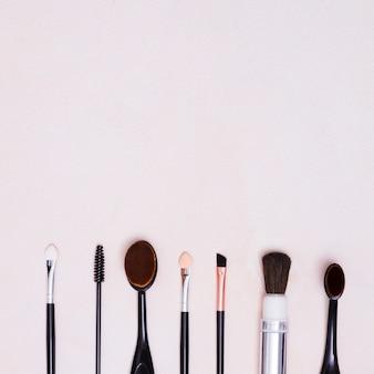 Tipi differenti di spazzole nella fila con lo spazio della copia su fondo bianco