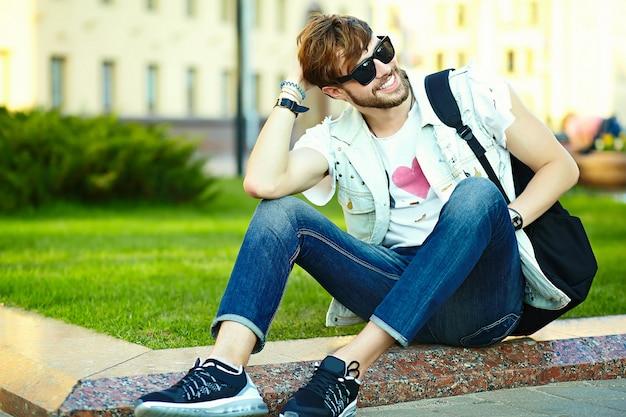 Tipo bello sorridente dell'uomo divertente dei pantaloni a vita bassa in panno alla moda di estate nella via che si siede sull'erba nel parco