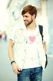 Tipo bello sorridente dell'uomo divertente dei pantaloni a vita bassa in panno alla moda di estate nella via