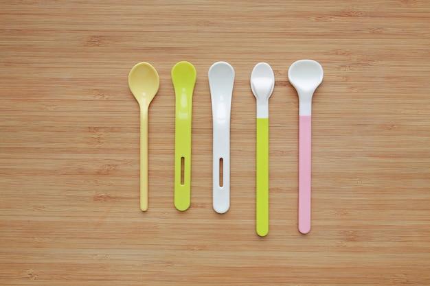 Tipo differente di cucchiai di plastica per i bambini sul fondo del bordo di legno.