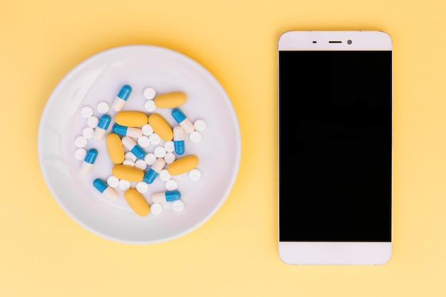 Tipo differente di pillole sul piatto bianco vicino allo smartphone su fondo giallo
