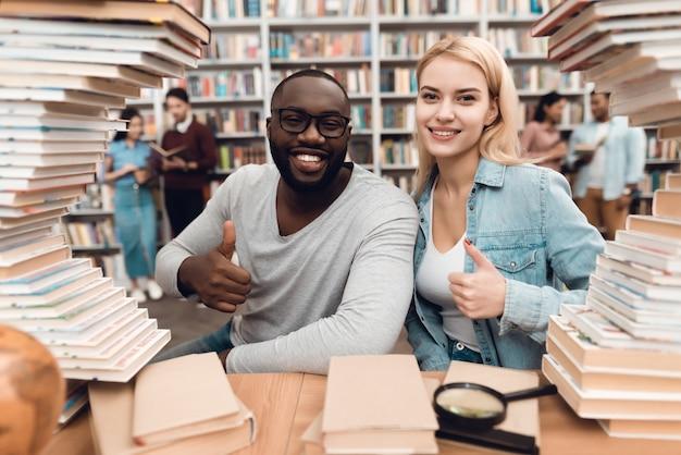 Tipo etnico afroamericano e ragazza bianca circondati dai libri in biblioteca. gli studenti stanno dando il pollice in alto.