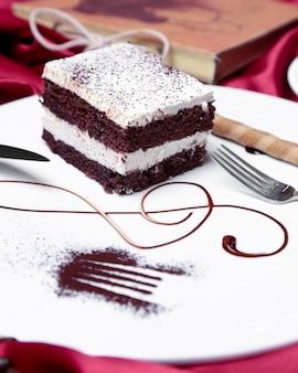 Tiramisù vista frontale con un waffle stick su un piatto con decorazioni e una forchetta