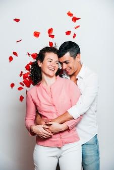 Tirante allegro che abbraccia signora sorridente fra i petali di lancio