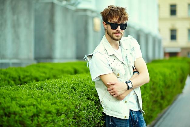 Tirante bello sorridente divertente dell'uomo bello dei pantaloni a vita bassa in panno alla moda di estate nella via in occhiali da sole