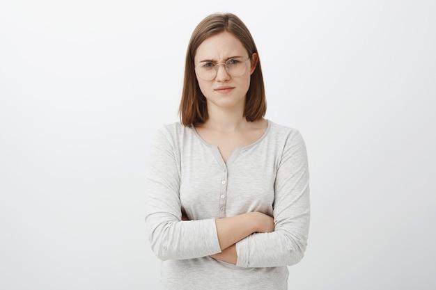 Tirante di pensiero della donna che si trova fissando sospettoso con incredulità. giovane femmina europea intelligente insicura intensa in occhiali aggrottando le sopracciglia tenendo le mani incrociate sul petto scontento pensare che parlare è una cazzata