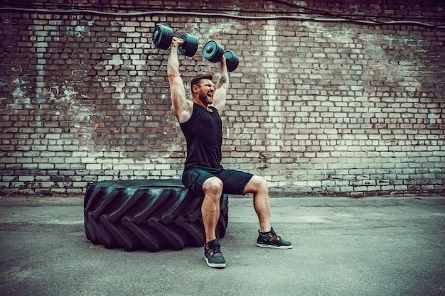 Tirante muscolare che fa le esercitazioni con il dumbbell contro un muro di mattoni