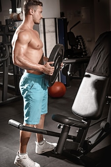 Tirante muscolare del bodybuilder che fa le esercitazioni con peso in ginnastica