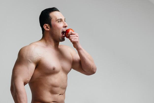 Tirante sexy sportivo che mangia frutta su una priorità bassa bianca. dieta. dieta sana