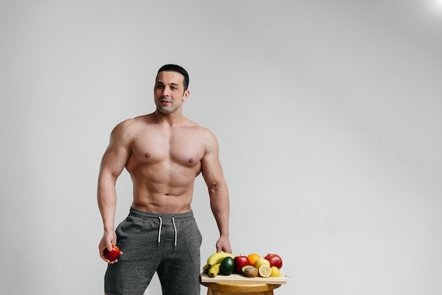 Tirante sexy sportivo che propone su una priorità bassa bianca con i frutti luminosi. dieta. dieta sana