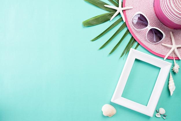 Tiri gli accessori in secco su pastello verde per il concetto di vacanza estiva.