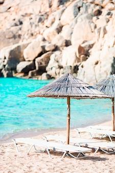 Tiri le sedie e gli ombrelli in legno per le vacanze sulla spiaggia in grecia