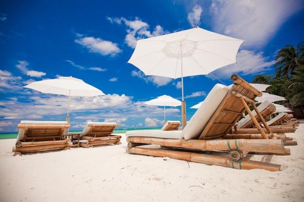 Tiri le sedie in legno in secco per le vacanze sulla spiaggia tropicale