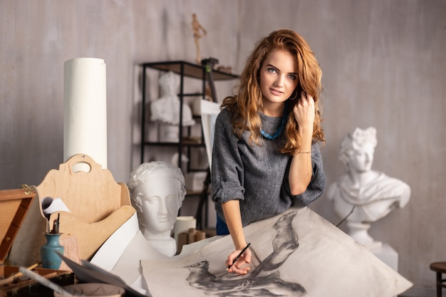 Tiro al coperto di artista femminile professionale dipinto su tela in studio.