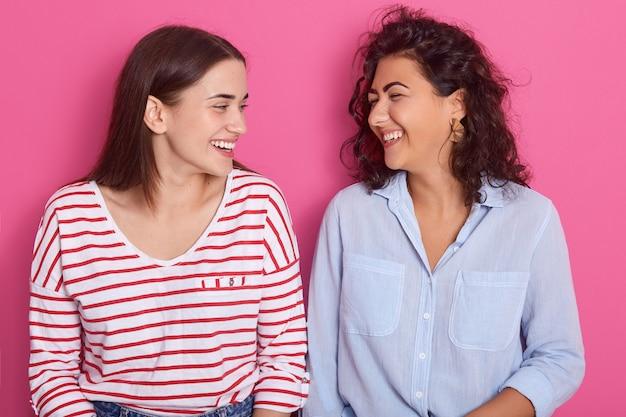 Tiro al coperto di belle donne con espressioni positive, guardarsi l'un l'altro, indossare abiti casual, modelle in posa su sfondo rosa. persone, emozioni, lesbiche, concetto di amore per lo stesso sesso.
